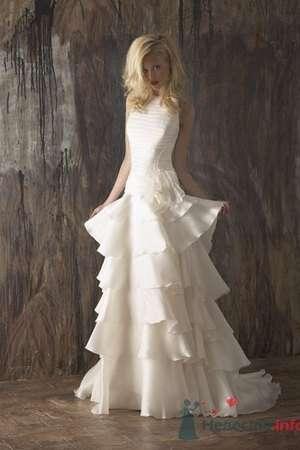 Необычное свадебное платье Model Novias с закрытым лифом, юбкой из воланов, шлейфом, декорированное цветком на талии в тон платья. - фото 188 simik