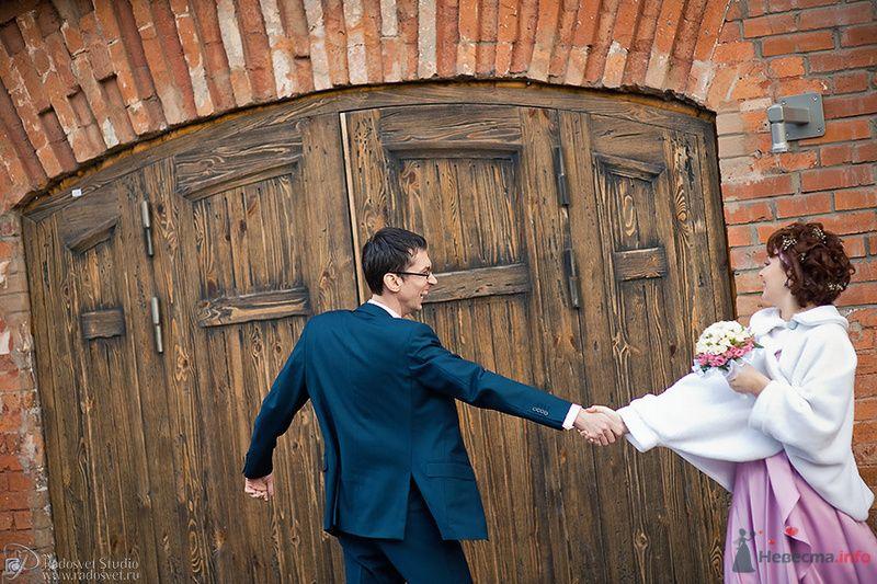 Жених и невеста, взявшись за руки,  стоят возле деревянной двери
