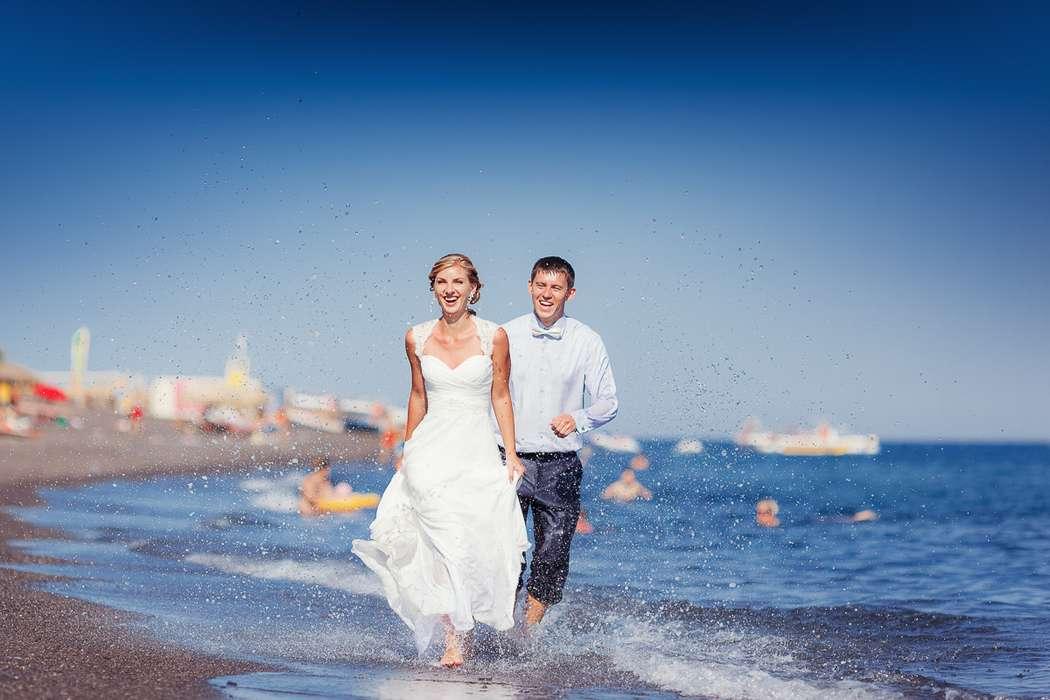 На берегу лазурного моря, жених и невеста бегут по воде босиком, на ней белое длинное платье, он в голубой рубашке и синих брюках - фото 2120972 Чунгуров Илья - фотограф