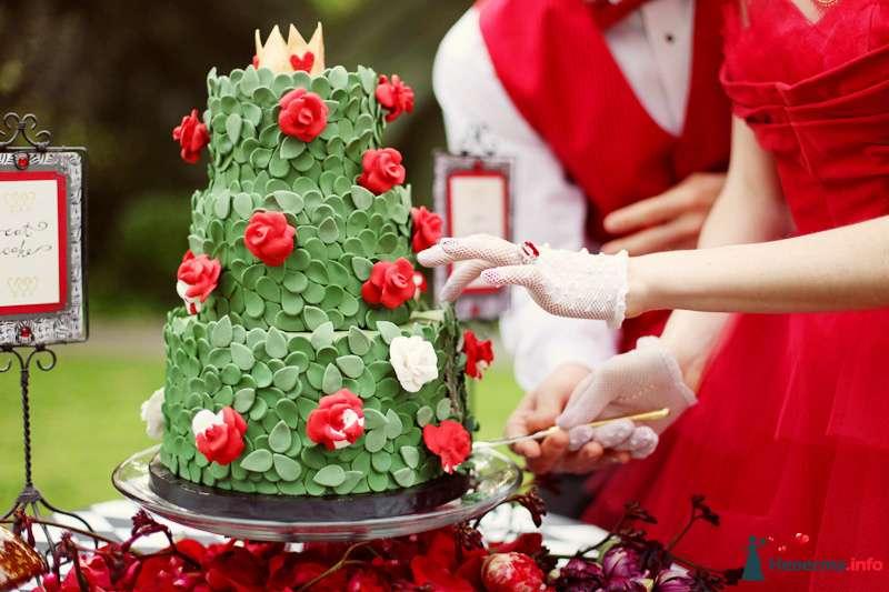 Жених с невестой, разрезающие   свадебный торт, украшенный зеленными сахарными листочками и красными розами - фото 113898 July87