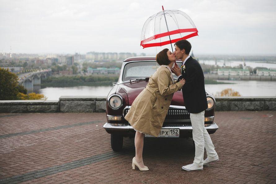 Жених и невеста, прислонившись друг к другу, стоят на фоне автомобиля под зонтом  - фото 3033843 Свадебные Волги - аренда авто