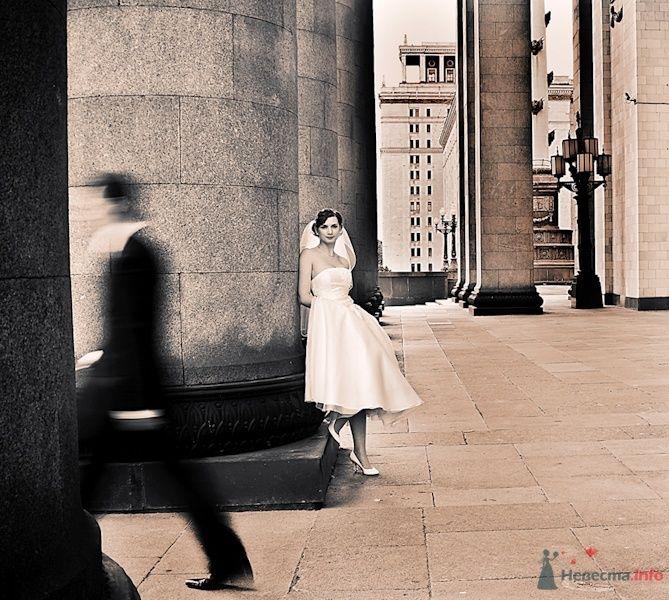 Невеста в белом платье стоит. прислонившись, к серой колонне