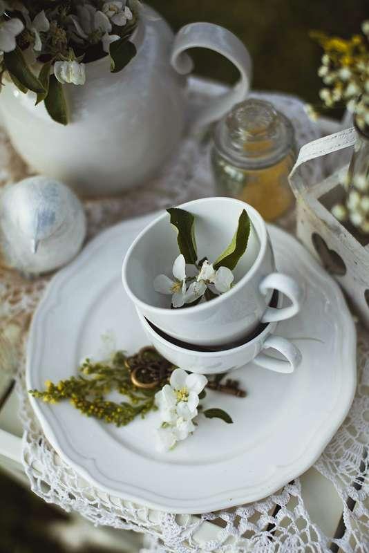 Белые фарфоровые чашки, наполненные цветами жасмина, белое блюдо, белая фигурка птички на белой ажурной салфетке, декор - фото 1934843 Свадебный фотограф Анна Алфёрова
