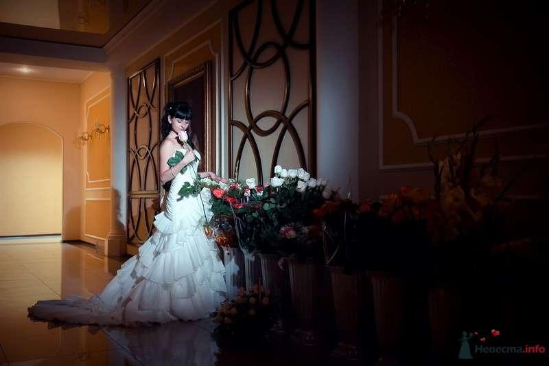 Невеста в белом длинном платье стоит возле больших ваз с розами - фото 75418 Невеста01