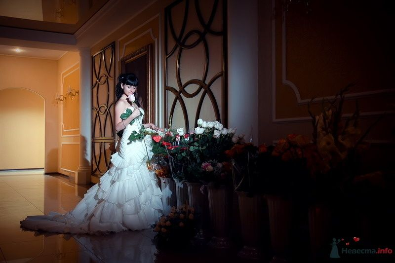 Невеста в белом длинном платье стоит возле больших ваз с розами