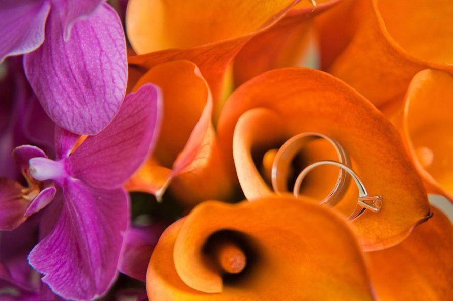 Обручальные кольца, выполненные в классическом стиле с бриллиантом, на фоне букета. - фото 665375 WedTour - свадьба в Тайланде и на Бали