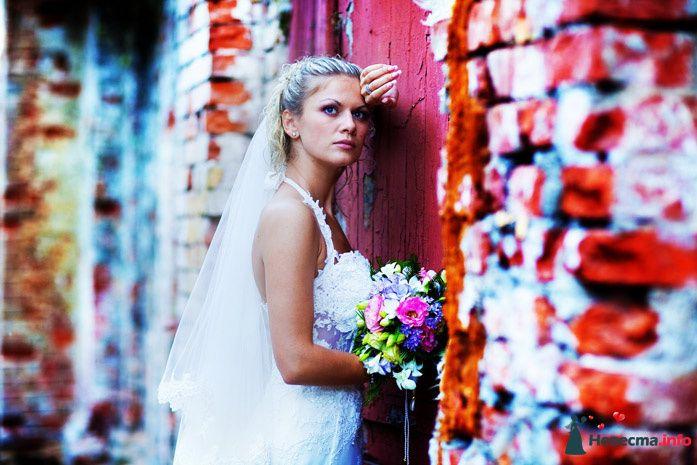 Невеста в белом длинном платье стоят возре яркой кирпичной стены