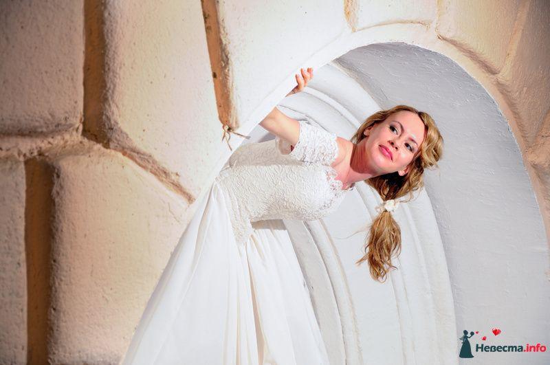 Невеста в белом длинном платье стоит возле круглой арки