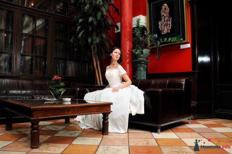 Невеста в белом длинном платье сидит на кожанном диване возле
