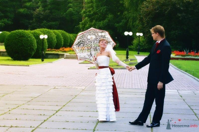 Жених и невеста, взявшись за руки,  стоят в парке, у нее у руках белый зонт - фото 61938 Dyagileva
