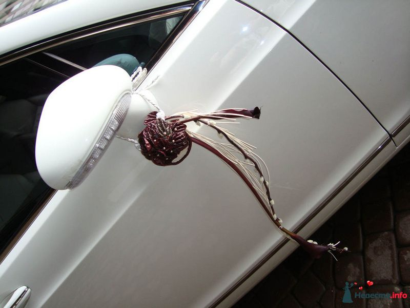 Белый свадебный автомобиль, украшенный оригинальной экибаной из белых орхидей и бело- бордовых шнурков на  боковых зеркалах. - фото 107400 Флорист-декоратор Янина Венгерова