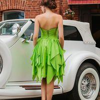 Возле белого ретромобиля подружка невесты в зеленом платье миди с открытой спиной и многоярусной юбкой в бежевых туфлях на шпильке