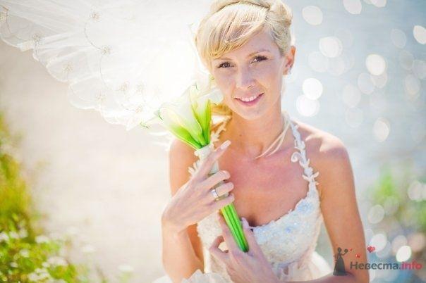 Невеста с букетом желтых цветов стоит в поле