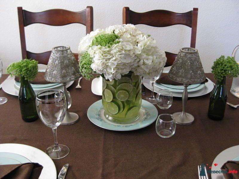 Букет из белых гортензий и вибурнума в стеклянной вазе с долькам лайма; по бокам - стеклянные бутылки с зеленью. - фото 90760 Missy