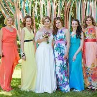 """Под деревом с лентами невеста в платье с вырезом """"Анжелика"""", заниженной талией, гипюровым рукавом три четверти держит букет и её подружки в длинных платьях кораллового, желтого,голубого цветов, белого с синими цветами и розового цветастого"""