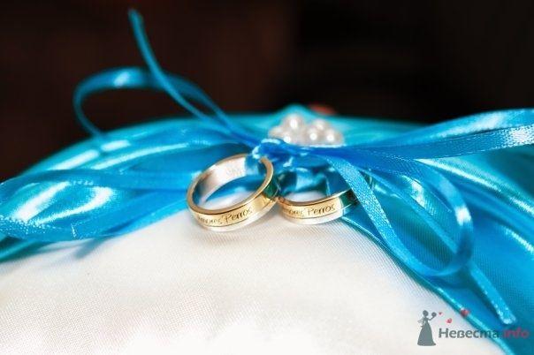 Золотые кольца из комбинированного золота с гравировкой на поверхности, на фоне голубых лент. - фото 61015 Jamaica