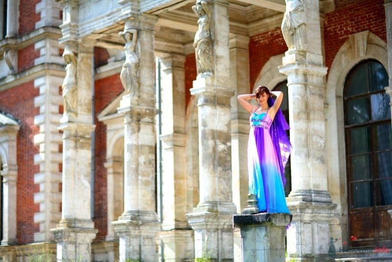 Невеста в ярком длинном платье стоит на фоне серого здания