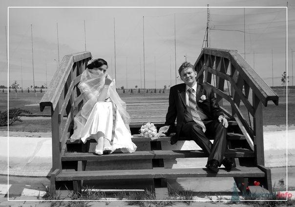 Жених и невеста сидят на улице на ступеньках