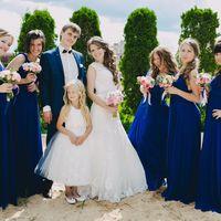 """Жених в синем костюме, бабочке обнимает невесту в платье А-образного силуэта рядом девочка в белом платье """"принцесса"""" и подружки в одинаковых синих длинных платьях держат букеты на пляже"""