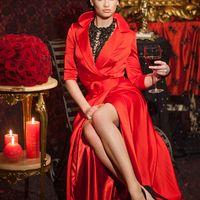 Подружка невесты в красном длинном платье с запахом на красном подкладе, с рукавом три четверти, поясом с пряжкой, в черных замшевых туфлях на шпильке и черном колье держит бокал.
