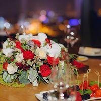 Цветочная композиция на стол повторяла букет невесты, а на каждой тарелке лежала именная карточка с семейным гербом и маленьким красным ронункулюсом, в народе лютиком.