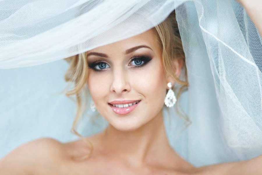 Романтический образ невесты выражен в прическе из длинных локонов собранных в низкий пучок на затылке с фатой, с макияжем в стиле - фото 1935335 Свадебные стилисты Art4Studio