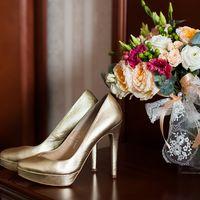 Туфли невесты золотого цвета  и свадебный букет на коричневой столешнице