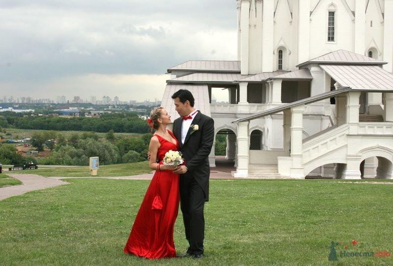 Жених и невеста стоят, прислонившись друг к другу, на фоне белого здания - фото 35127 YuBinLi