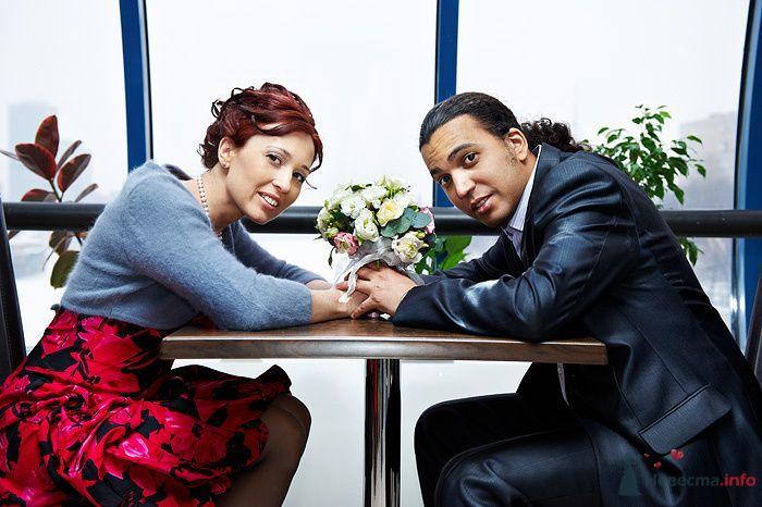 Жених и невеста сидят, взявшись за руки, за столиком в кафе - фото 78931 Студия свадебной фотографии Сергея Рыжова