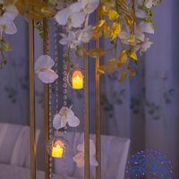 Декор столов гостей- стойки- скелетоны с декоративными комопозициями и свечой в прозрачном шаре.
