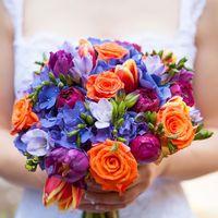 Яркий букет невесты из оранжевых роз, красных тюльпанов, сиреневых фрезий, синих гортензий и малиновых пионов