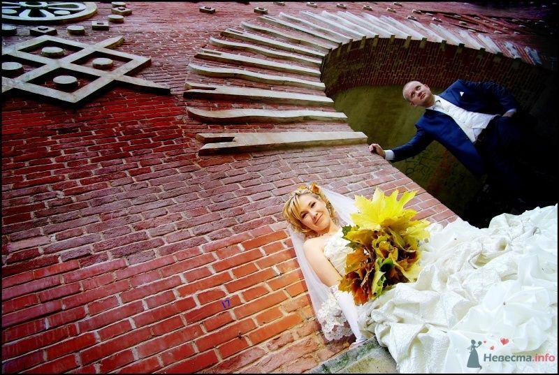 Жених и невеста, с букетом желтых листьев, стоят на фоне кирпичной
