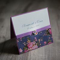 свадебное приглашение в лиловых (сиреневых) тонах, украшенное пряжкой с камнями, атласной лентой, на перламутровый картон теплого белого цвета нанесены имена жениха и невесты, основа приглашения в цвет ленты, нижняя часть приглашения декорирована цветным