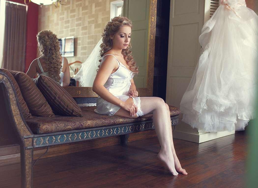 Невеста в атласной комбинации одевает на ногу белую кружевную подвязку - фото 2603959 Фотограф Дюбайлов Максим