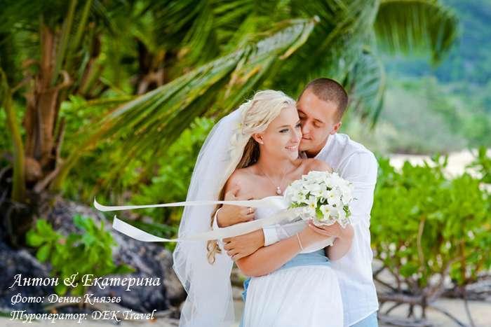 На тропическом побережье стоит влюбленная пара, невеста в белоснежном платье и воздушной фате держит в руках букет цветов, жених - фото 2771711 Dek Travel - свадьба на Сейшелах и Маврикии