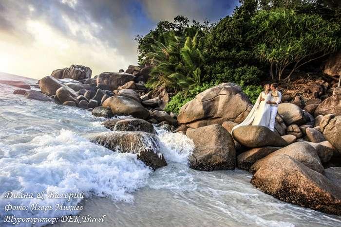 На каменистом берегу тропического океана стоят молодожены, невеста в белом длинном платье повернула голову к жениху в белом - фото 2771755 Dek Travel - свадьба на Сейшелах и Маврикии