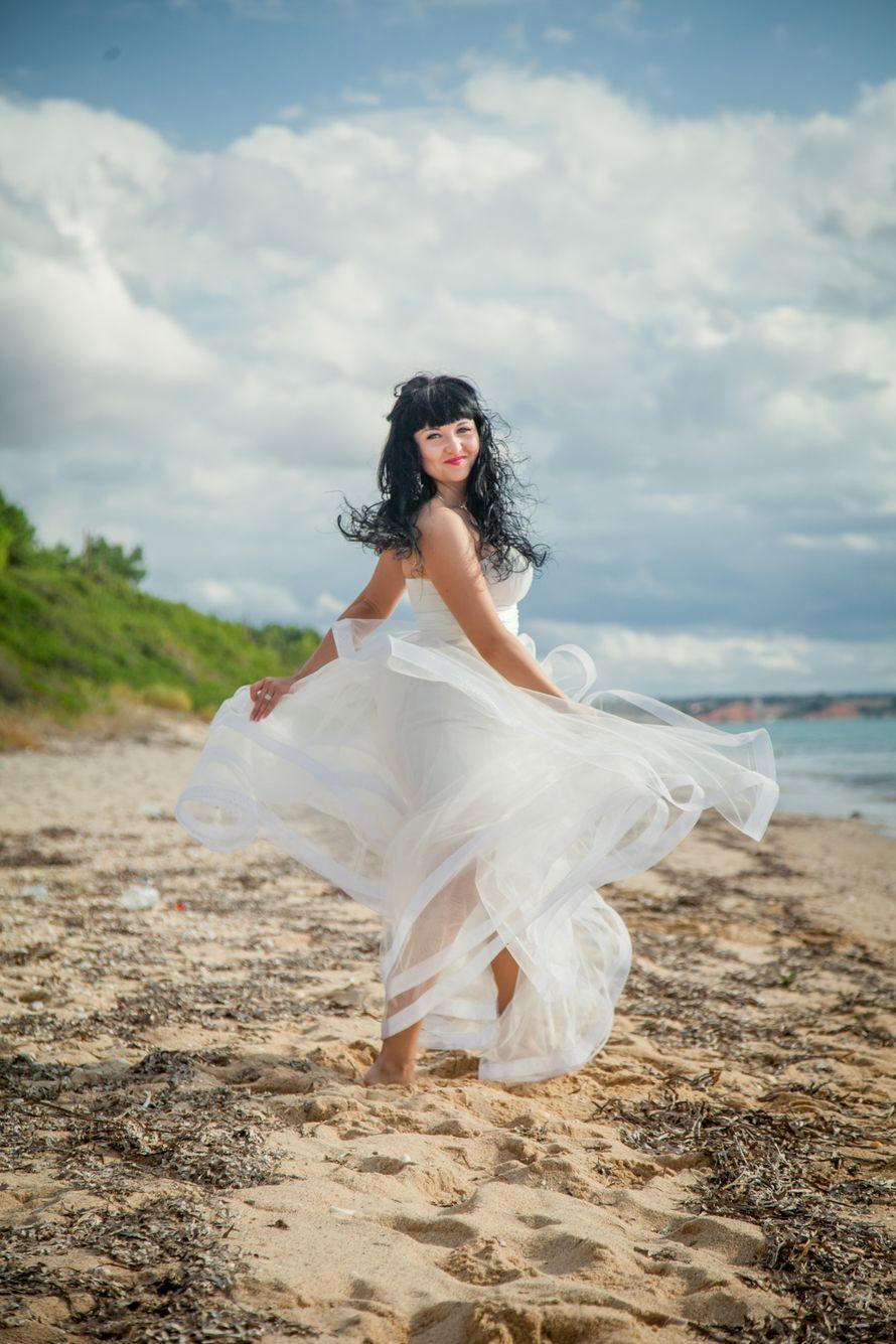 По песчаному побережью босиком гуляет невеста в  белом платье из органзы, оглядываясь назад, она развевает на ветру подол - фото 2818445 Фотограф Дамианос Максимов
