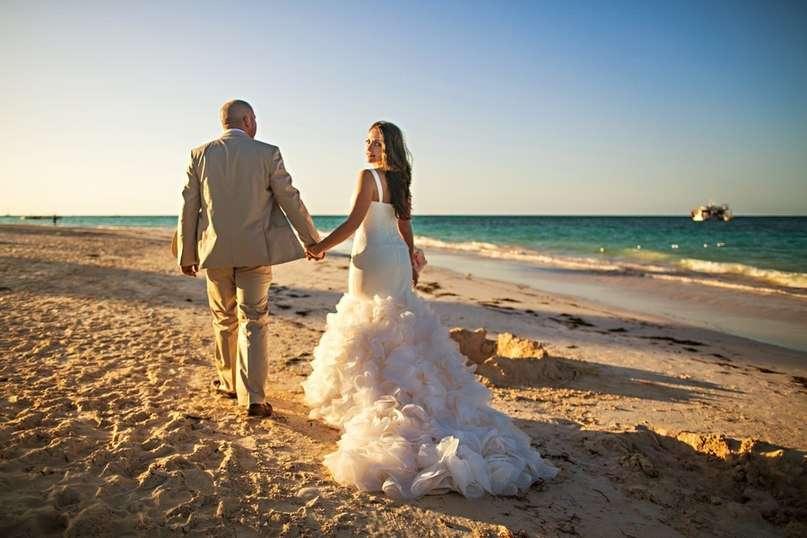 По песчаному пляжу вдоль берега идут молодожены, взявшись за руки, жених в светлом костюме, невеста в белоснежном платье с пышным - фото 2842069 Destiny dress - show room, свадебные платья