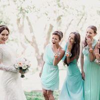 В саду подружки невесты в платьях мятных оттенков коротком и длинных в греческом стиле с цветочными браслетами смотрят на невесту с диадемой в фате, платье с длинным рукавом из гипюра и букетом из белых цветов