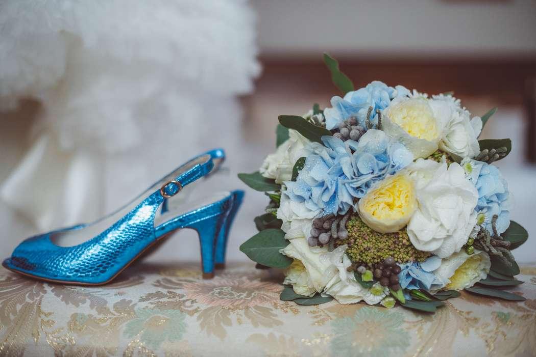 Синие босоножки на небольшом каблуке стоят на спинке дивана рядом с букетом цветов. - фото 3267693 Фотограф Демьянова Илона