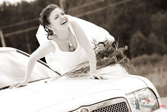 Невеста в длинном белом платье сидит на машине