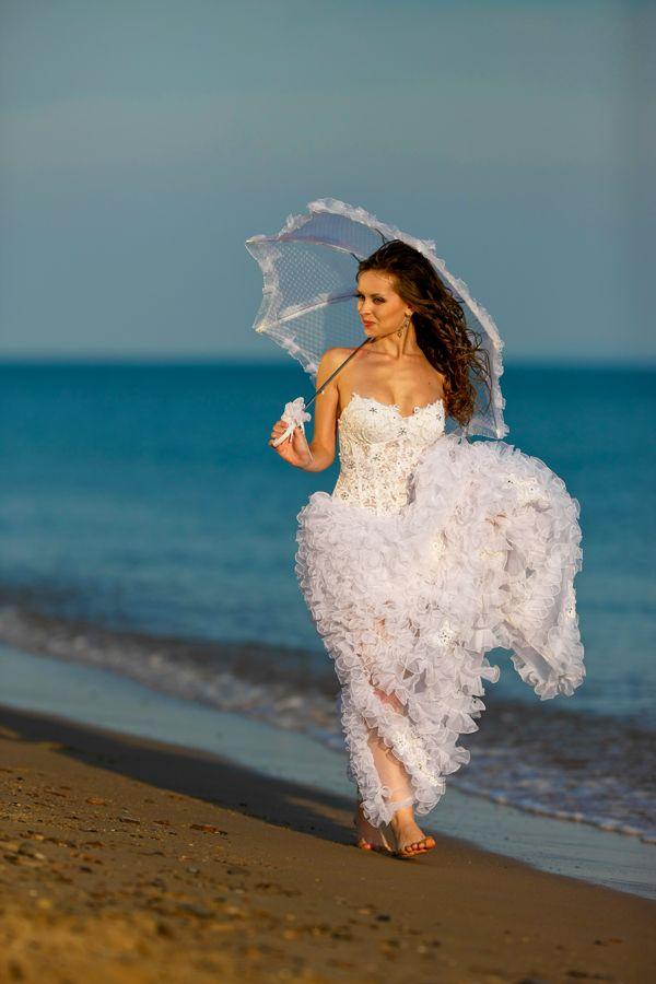 Невеста в красивом ажурном пышном белом платье держит в руке зонтик от солнца прогуливаясь по берегу моря - фото 542973 Фотограф Николай Хорьков
