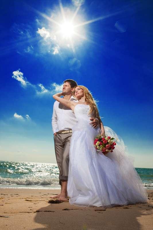 Жених в серебристых подкаченных брюках и белой рубашке обнимает за талию невесту в белом пышном платье с букетом цветов в руке - фото 600222 Фотограф Николай Хорьков