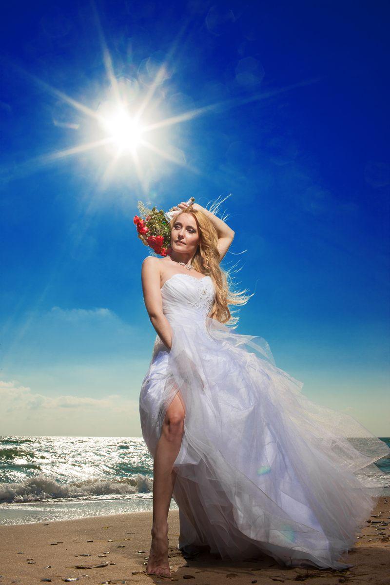 Невеста в белом платье стоит босиком на пляжном песке с букетом из красных цветов - фото 600226 Фотограф Николай Хорьков