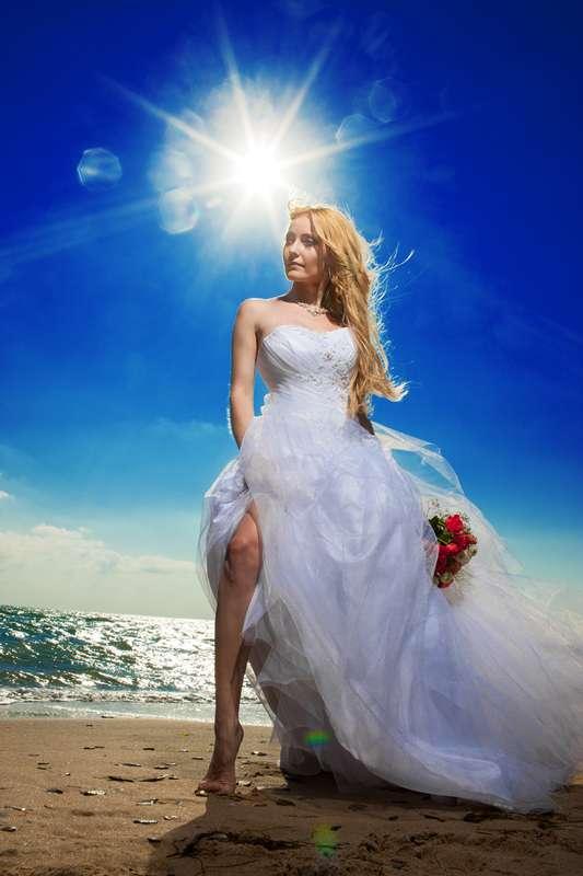 Невеста в белом пышном платье с корсетом стоит на пляже босиком в руке ее красный букет - фото 600229 Фотограф Николай Хорьков