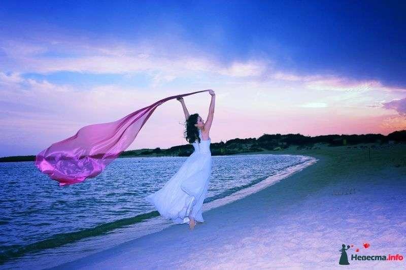 Невеста бежит по пляжу вдоль моря в белом платье, в руках у нее розовая фата развевающаяся волнами на ветру - фото 362000 algeka