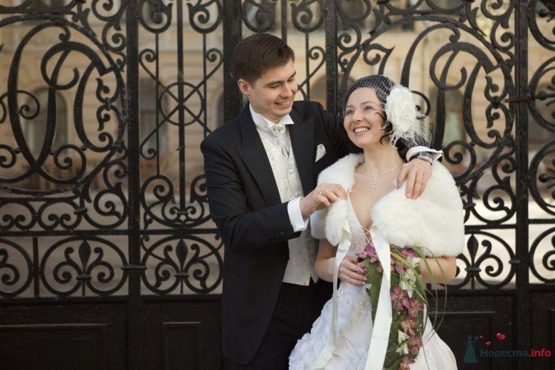 Жених и невеста, прислонившись друг к другу, стоят на фоне ограждения - фото 25352 Эльмира