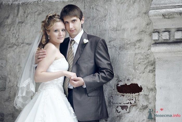Жених и невеста стоят, прислонившись друг к другу, на фоне старой