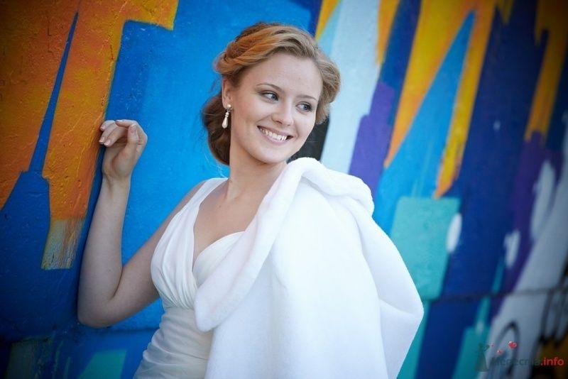 Невеста в белом платье стоит возле ярко разрисованной стены