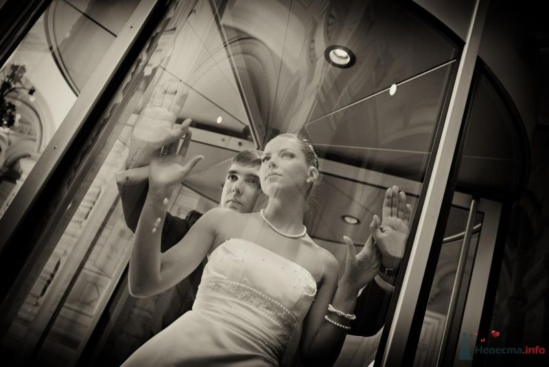 Жених и невеста, прислонившись друг к другу, стоят в комнате возле зеркала - фото 50229 Skycat